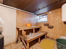 Kellarikerroksessa sauna, jossa puukiuas ja muuripata