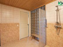 Lasitiiliseinä tuo luonnonvaloa kokonaan laatoitettuun kylpyhuoneeseen
