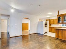 Näkymä olohuoneesta keittiöön ja takkahuoneeseen