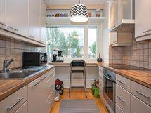 Keittiössä laadukkaat kodinkoneet. Ikkunasta avara näkymä sisäpihan puolelle.