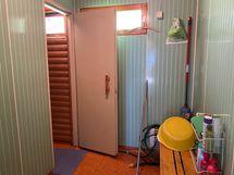 Saunan tilava pesuhuone, saunan ovi takavasemmalla.