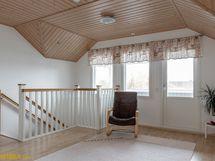 Tilava yläkerran aula, josta käynti lasitetulle parvekkeelle.