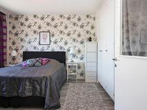 Makuuhuoneessa kauniit tapetit ja säilytykseen tilava vaatehuone.