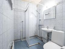 Laatoitetttu kylpyhuone, jonne mahtuu myös pesukone