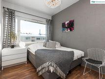 Tyylikäs harmain sävyin sisustettu makuuhuone