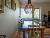 Kulmaikkunan eteen olohuoneessa mahtuu iso ruokapöytä. Ovi johtaa lasitetulle parvekkeelle.