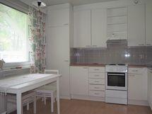 Tilava valoisa keittiö, joka avautuu olohuoneeseen