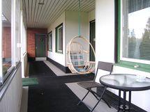 sisäänkäynnin edessä katettu lasiovin varustettu terassi