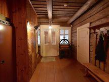 Eteinen, josta käynnit jakautuvat eri huoneisiin. Ilmalämmityskone vasemmalla hoitaa lämmityksen talossa.