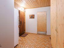 Yhteinen eteinen, puinen ovi johtaa varastosta tehtyyn huoneeseen.