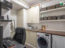 Kodinhoitohuoneeseen käydään eteisestä. Siistiä tilaa on hyödynnetty myös kotitoimistona.