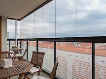Asunnon tilava lasitettu parveke - näkymä yli kattojen