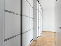Eteisessä ja olohuoneessa on koko seinän levyinen liukuovikaapisto.