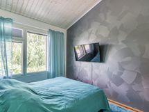 Makuuhuoneessa kiva tehosteseinä ja korkeutta tuo vinokatto