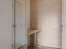Eteisen ja kylpyhuoneen välinen tila, jossa peilikaappi sekä sähköpöytä