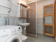 Kylpyhuoneessa suihku ja tila pesukoneelle