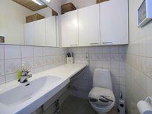 Erillinen laatoitettu wc kalusteineen.