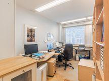 kirjahyllyllä jaettu toimisto huone