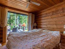 Isompi makuuhuone josta käynti terassille