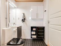Kylpyhuoneen sävymaailma on ajaton ja kaappitilaa löytyy.