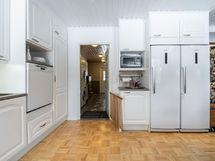 Keittiöstä kulku kodinhoitohuoneeseen, autotalliin ja kylpyhuoneeseen