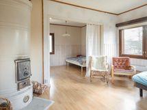 piharakennuksen olohuone ja pönttöuuni sekä makuualkovi