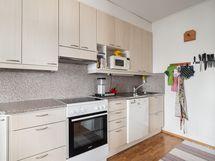 Keittiö jossa paljon työpöytä tilaa kokkailla ja leipoa