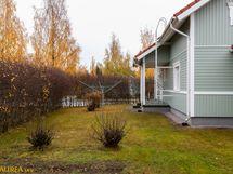 Julkisivu takapihalta. Suojaisa pensasaita, joka reunustaa takapihaa ja sivupihaa.