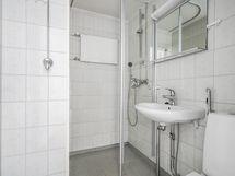 Siisti kylpyhuone jossa pesukoneliitäntä. Lattiassa pinnoite