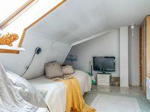 Yläkerran suurempi makuuhuone, joka voidaan jakaa kirjahyllyjen kohdalta kahtia.