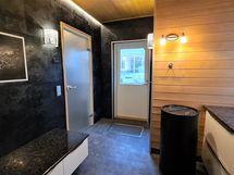 Pukeutumistilassa vesipiste, kivitasot ja pyykkitorni