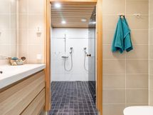 alakerran erillinen wc, taustalla pesuhuonetta