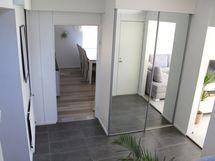 Eteiskäytävästä päästään aulaan, josta on kulku alakerran huoneisiin ja yläkertaan.