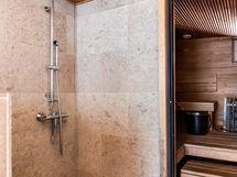 Kylpyhuoneen kaunis travertiinilaatoitus, katossa sormipaneelia.