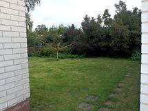 Talon ja autotallin välistä takapihalle.
