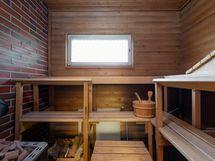 Viihtyisä tilava sauna puulämmitteisellä kiukaalla. Sähkökiuas valmius.