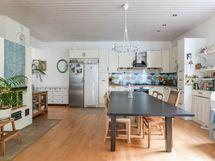 Uuden puolen keittiö ja ruokatila, jossa on tilaa isollekin ruokapöydälle.