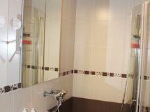 Eteiskäytävän päässä ja keittiön vieressä sijaitsee tyylikkäästi remontoitu kylpyhuone.