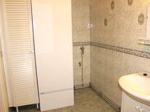 Kylpyhuoneessa on hyvä tila pyykinpesupisteelle pyykkikaappeineen.