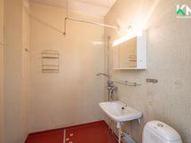 Kylpyhuone on ilmeeltään vaalea. Ovensuusta vasemalla puolella on paikka pesukoneelle ja kuivausrummulle.