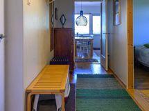 Vasemmalle jää ulko-ovi ja oikealle avautuu keittiö. Takana näkyy olohuoneen iso ruokapöytä.