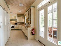 Taustalla keittiö, oikealla ovet lasitetulle terassille.
