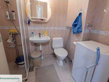 Kylpyhuoneessa suihkukaappi ja pesukoneliitäntä