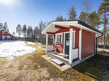 Kotitalon ja grillikatoksen välissä sijaitsee eristetty nukkuma-aittarakennus.