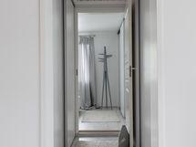 Yläkerran aulasta kulku isoon makuuhuoneeseen, käytävässä säilytystilaa molemmin puolin.