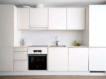 Moderni, tyylikäs keittiö jossa paljon säilytystilaa