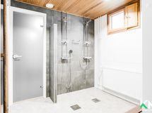 Taloyhtiön juuri remontoitu yhteisen saunatilan kylpyhuone.