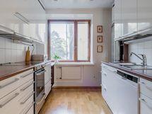 Hyvin varusteltu keittiö jonka ikkunat rauhaisalle sisäpihalle