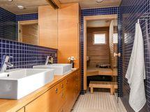 Kylpyhuoneessa tyylikäs tammitaso ja kaksi allasta