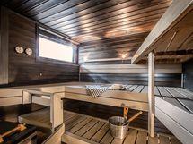 Tilava sauna lasiseinällä